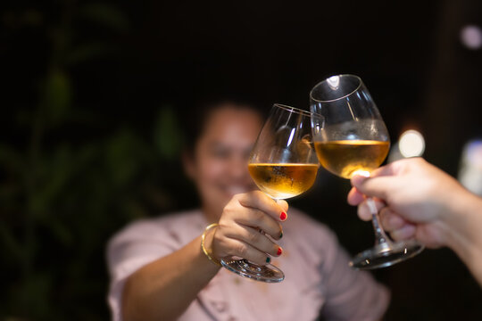 Shot in high iso with low light couple toasting wineglasses on vacation.