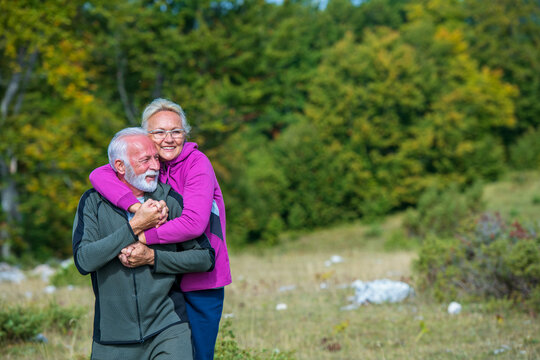 Happy senior couple smiling outdoors in nature. Grandparents, autumn.