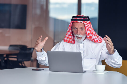 Arab businessman looks surprised while using a laptop