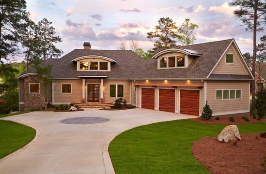 Exterior of beautiful modern home with dormer windows in roof and long driveway