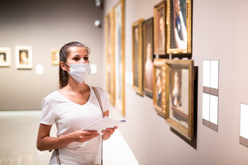 Focused adult girl in disposable face mask admiring paintings in museum holding brochure with...