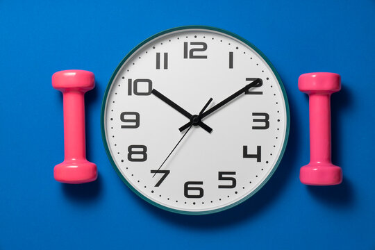 Time for exercising clock and dumbbell with blue yoga mat background