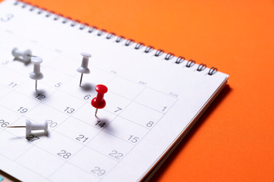 close up of calendar on the orange table background, planning for business meeting or travel planning concept