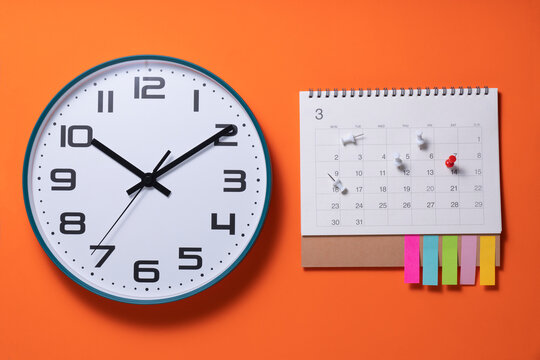 close up of clock calendar on the orange table, planning for business meeting or travel planning concept