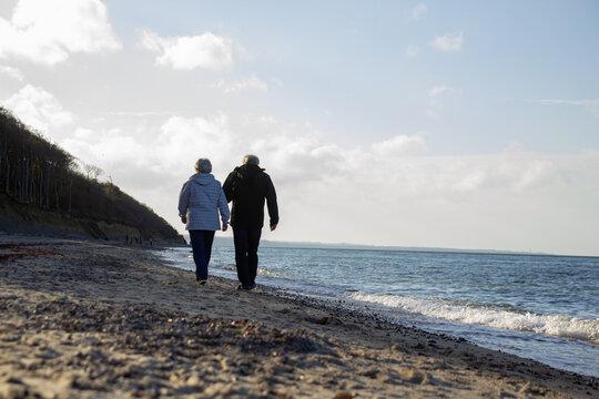 Rentner Ehepaar geht am Strand am Meer Hand in Hand spazieren