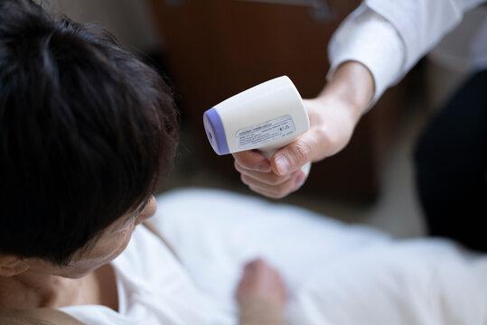 医者が高齢女性の額にデジタル体温計を当てている。