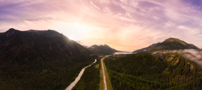 Picturesque Panoramic View of Scenic Road from Above alongside Winding Glacial River. Dramatic Sunrise Sky. Aerial Drone Shot. Alaska Highway in the Northern Rockies, British Columbia, Canada.