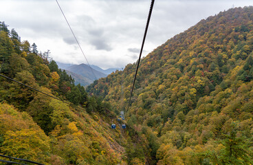 View of mountains and valleys from the Dragondola (Naeba-Tashiro Gondola) in autumn foliage season. Longest aerial gondola lift line in Japan. Naeba, Yuzawa, Niigata Prefecture, Japan.