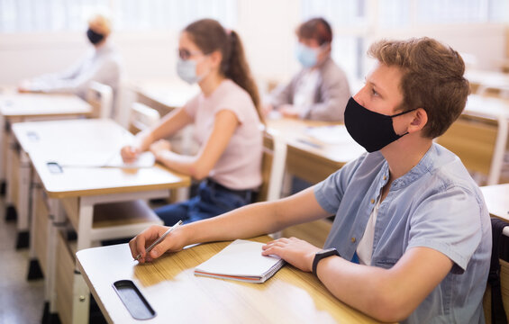 Portrait of diligent schoolboy wearing protective face mask sitting in class working with classmates, new normal education during pandemic