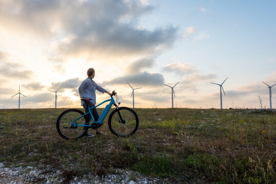 Woman with a bike in the nature / A woman with an electric bike enjoys the sunset against the backdrop of wind turbines. Green energy, sustainable alternative electricity, no pollution environment.
