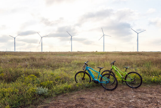 Amazing view with electric bikes in a field against the backdrop of wind turbines. Green energy, sustainable alternative electricity, no pollution environment.
