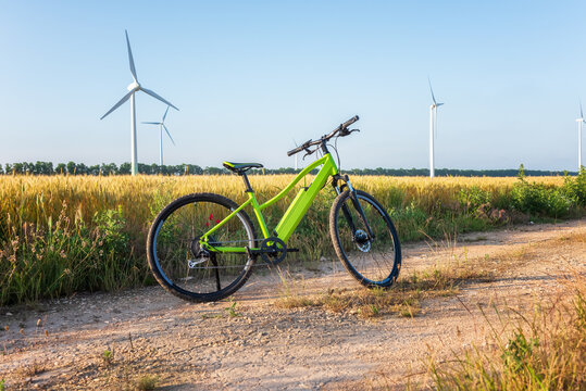 Amazing view with an electric bike in a field against the backdrop of wind turbines. Green energy, sustainable alternative electricity, no pollution environment.