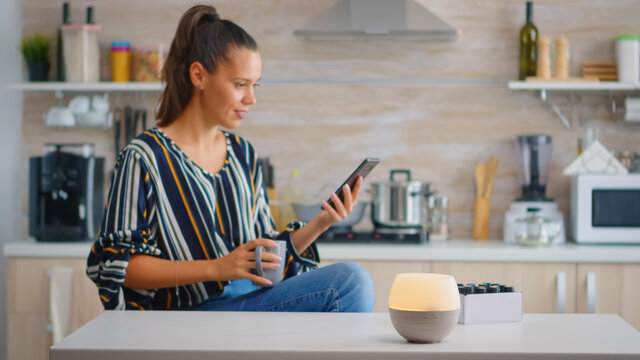 Woman enjoying aromatherapy with essential oils diffuser working while she drinks coffe. Aroma health essence, welness aromatherapy home spa fragrance tranquil theraphy, therapeutic steam, mental