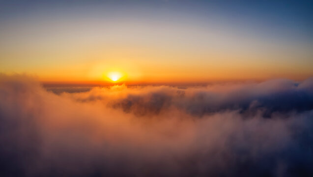 Aerial point of view of a golden sunset above the clouds