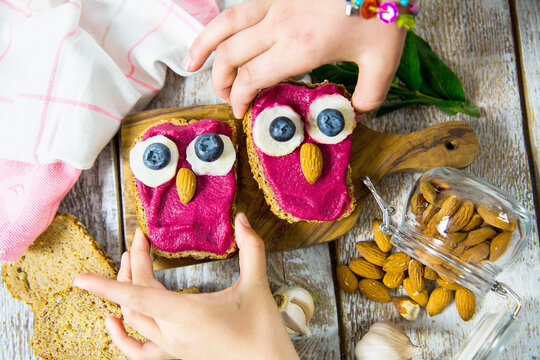 Fun food for kids - cute little owls shaped sandwiches. Spread of beets, chickpeas, almonds and garlic