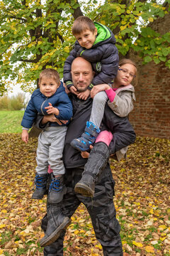 The father is carrying three children. Father carrying childs piggyback. The father plays with the childrens on an autumn day