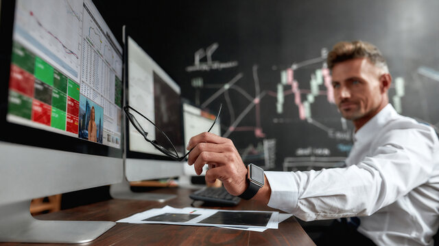 A bright rewarding relationship. Middle-aged trader sitting by desk in front of multiple monitors while working in the office. His colleague and blackboard full of data analyses in background.