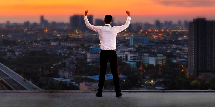 Businessman standing on roof and looking at Cityscape skyline at sunset