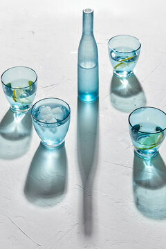 drink, detox and diet concept - blue glasses with water, lemons and ice on white background