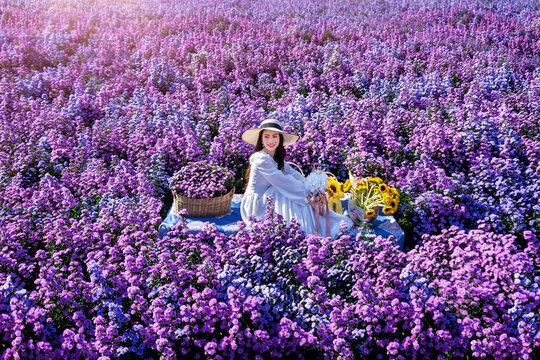 Beautiful girl in white dress sitting in Margaret flowers fields, Chiang Mai.