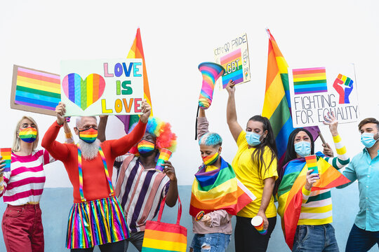 Happy Multiracial people wearing face mask celebrating at gay pride festival during corona virus - Group of friends with different age and race fighting for gender equality