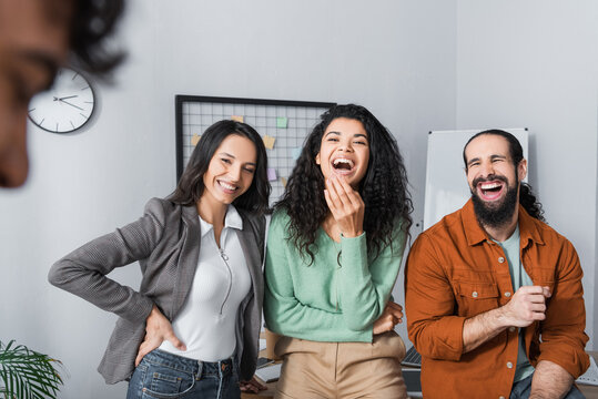 laughing hispanic businesspeople looking at colleague on blurred foreground