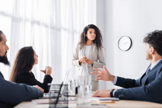 Hispanic businesswoman standing and looking at colleague gesturing during business meeting on blurred foreground