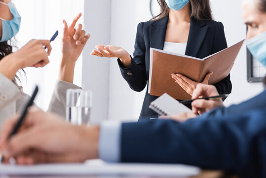 Businesswoman in medical mask holding paper folder near hispanic colleagues on blurred foreground during meeting