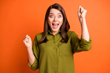 Photo of amazed young funny lady raise fists open mouth wear green shirt isolated orange color...