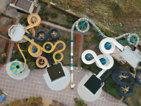 Aerial photo of small aqua park with colorful tubes, view from above, abandoned, nobody