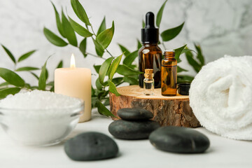 beauty treatment items for spa procedures on white wooden table with green plant. massage stones,...