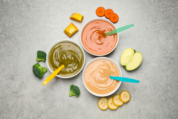 Healthy baby food and ingredients on grey table, flat lay