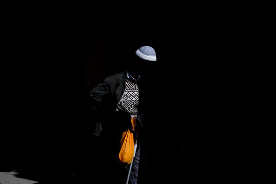Person Wearing Knit Hat Standing Against Black Background