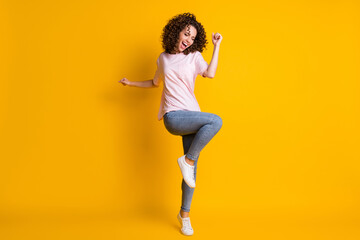 Photo portrait full body view of cheerful girl dancing standing on one leg isolated on vivid yellow...