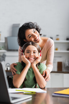 Smiling hispanic woman hugging daughter sitting at table with laptop in kitchen on blurred foreground