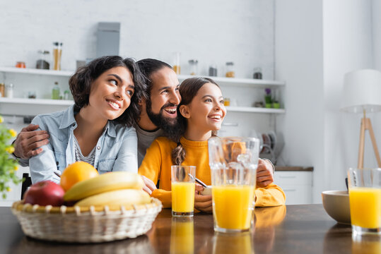 Cheerful hispanic man hugging family near breakfast and orange juice on kitchen table