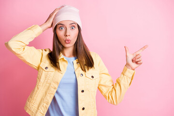 Photo of shocked brown haired girl wear pink hat point empty space hand head isolated on bright pink color background Wall mural