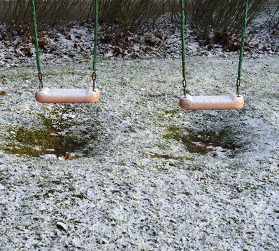 children's swing in the yard covered with the snow