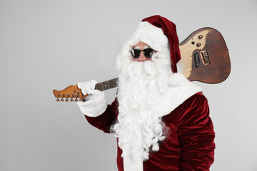 Santa Claus with electric guitar on light grey background. Christmas music