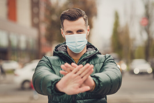 Portrait of serious gut show arms palms stop rejection discrimination wear safe medical healthcare mask outdoors