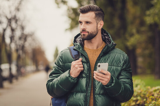Portrait of good looking young guy hold rucksack look far away good mood autumn travel sightseeing outdoors