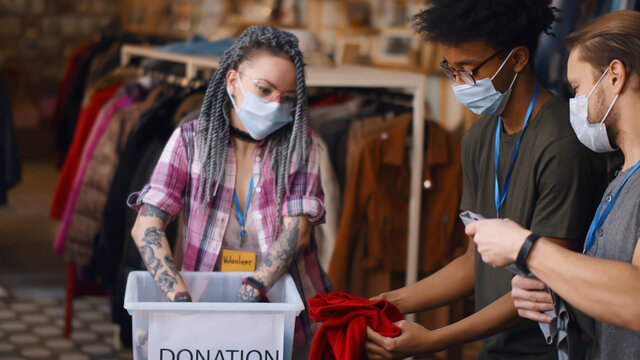 Happy young diverse volunteers in safety mask packing clothes in boxes for charity