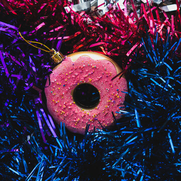Christmas bauble in the shape of doughnut on the  holographic abstract purple, blue and red tinsel. Trendy vaporwave creative gradient.