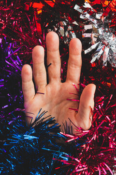 palm hand on the  holographic abstract purple, blue and red tinsel. Trendy vaporwave creative gradient.