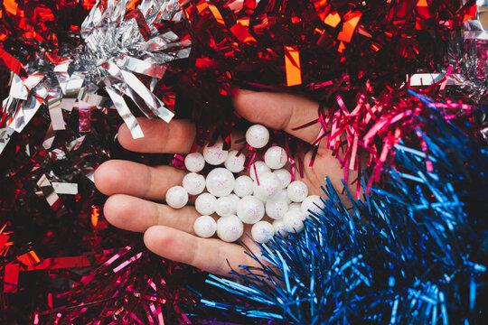 hand holds christmas bauble in the shape of white snowflake balls on the  holographic abstract purple, blue and red tinsel. Trendy vaporwave creative gradient.