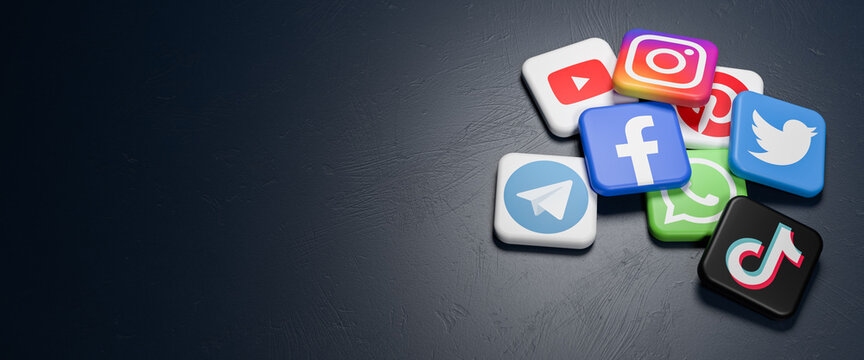 Logos of the major social media and messaging sites (Youtube, Instagram, Pinterest, Twitter, Facebook, Whatsapp, Telegram, Tiktok) on a heap on a dark table. Copy space - Web banner size