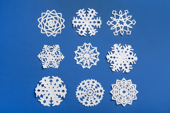 Many paper snowflakes on blue background, flat lay