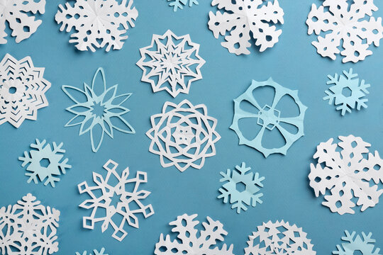 Many paper snowflakes on turquoise background, flat lay