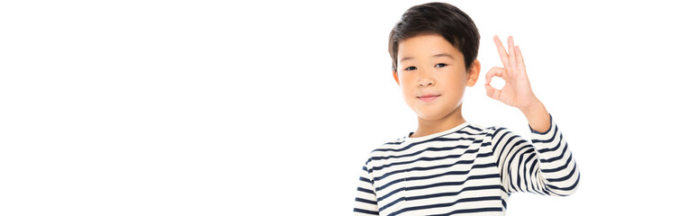Asian schoolboy showing okay gesture and looking at camera isolated on white, banner