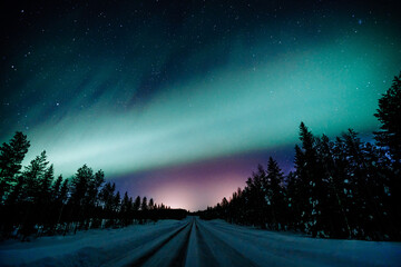 Northern lights Aurora Borealis activity over the road in winter Finland